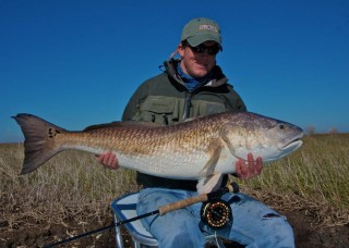 Capt. Andy Parker with a #36 bull red caught on fly